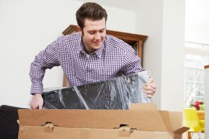Washington man packing tv safely in a tv box is the best way to store a tv for moving and self storage moving boxes