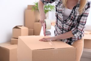 Woman using new boxes for long term self storage so her items won't get damaged.