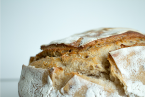 Close up of crusty homemade bread in front of a white background.