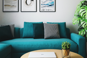 Green couch sitting in living room with beige wood table in front of it and three pictures hanging above it.
