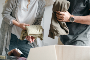 A man and a woman holding folded clothing, putting them in a cardboard box.