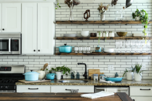 White kitchen with open shelving with plants, plates, and cups on it - a great way to get extra household storage space.