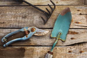 A blue garden spade, shears, and mini rake covered in rust sitting on top of a wooden table getting ready for garden tool storage.